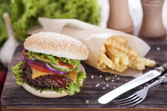 Beef burgers on a wooden board with chips and aromatic spices. Stock Photo