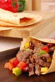 Beef burrito wrap sandwich close up. Beef burrito wrap sandwich on wooden tray closeup with ingredients background Stock Photos