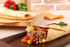 Beef burrito wrap sandwich with ingredients. Beef burrito wrap sandwich on wooden tray with ingredients background Royalty Free Stock Photography