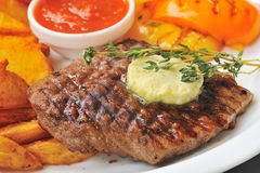 Beef and butter. Roasted beef steak with butter and savory stock image