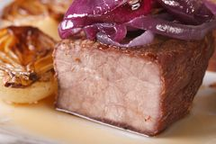 Beef with caramelized red onion on a plate macro. horizontal Royalty Free Stock Photo