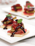 Beef Carpaccio bites on parmesan. Beef Carpaccio with grilled red pepper and zucchini bites on parmesan cheese with balsamic glaze stock images