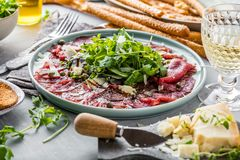 Beef carpaccio on black plate with mustard and parmesan. stock image