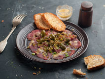 Beef carpaccio. With capers on dark background, selective focus stock photo