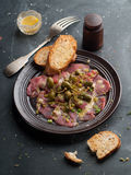 Beef carpaccio. With capers on dark background, selective focus royalty free stock image
