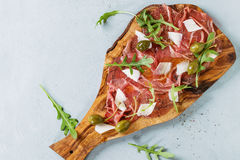 Beef carpaccio with capers. Beef carpaccio on olive wood serving board with capers, olive oil cheese and arugula, served over blue stone texture background. Top stock photo