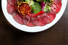 Beef carpaccio with lemon, hot red pepper and pepper jalapeno. royalty free stock images