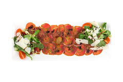 Beef carpaccio with olives and parmesan. Isolated on white background. Clipping path Stock Image