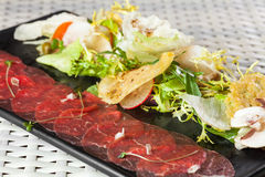 Beef carpaccio with parmesan cheese, capers and Royalty Free Stock Photo