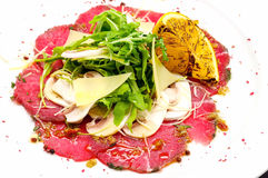 Beef carpaccio with Parmesan cheese. And herbs on a plate stock image