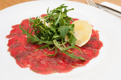 Beef Carpaccio. With Parmesan Cheese, Lemon and Wild Rocket - Shallow Depth of Field royalty free stock images
