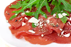 Beef carpaccio with pepper, rucola and parmesan Stock Photography
