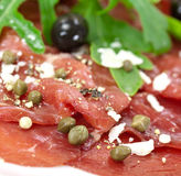 Beef carpaccio with pepper, rucola and parmesan Royalty Free Stock Images