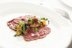 Beef carpaccio plated starter Stock Photography