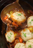 Beef Casserole with Dumplings. Slow-cooked beef stew with suet dumplings. Selective focus on the dumpling in the ladle Royalty Free Stock Photography