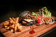 Beef charcoal black burger with french fries cheese and vegetabl Royalty Free Stock Images