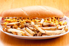 Beef and cheddar sandwich with fries. Beef and cheddar sandwich with hand cut french fries Royalty Free Stock Image