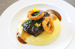 Beef cheeks dish. Braised beef cheeks in red wine. Mashed potatoes, spinach and onion rings Stock Photography