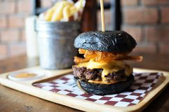 Beef cheese burger in charcoal bun on wooden plate. Stock Photography