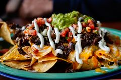 Beef and cheese corn nachos served on a big plate ready to eat. Image