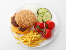 Beef Cheese Hamburger with French Fries. Lettuce, tomato, onion, cucumber, ketchup and mayonnaise on white background. View from above Royalty Free Stock Image