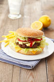 Beef Cheese Hamburger with French Fries. Lettuce, tomato, onion, cucumber, ketchup and mayonnaise on wooden table Royalty Free Stock Photo