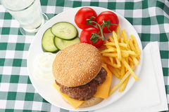 Beef Cheese Hamburger with French Fries. Lettuce, tomato, onion, cucumber, ketchup and mayonnaise on wooden table Royalty Free Stock Photos