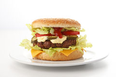Beef Cheese Hamburger. With lettuce, tomato, onion, cucumber, ketchup and mayonnaise, isolated on white Royalty Free Stock Images