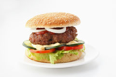 Beef Cheese Hamburger. With lettuce, tomato, onion, cucumber, ketchup and mayonnaise, isolated on white Royalty Free Stock Photo