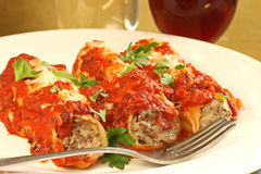 Beef and Cheese Manicotti. Beef and cheesy manicotti on plate with red wine and glass of water Royalty Free Stock Photos