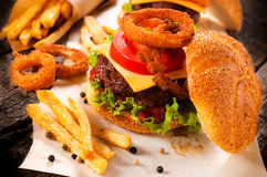 Beef cheeseburger. Big and tasty cheesburger with onion rings and french fries.Selective focus on the cheeseburger Royalty Free Stock Photos