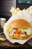 Beef cheeseburger with tomato, lettuce and french fries stock photography