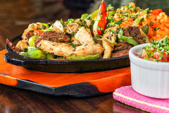 Beef and chicken fajitas. Mexican cuisine beef and chicken fajitas on a hot plate Stock Photography