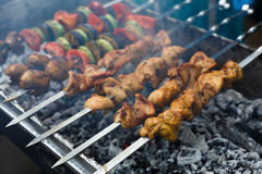 Beef and chicken kebab. Fresh meat at grill, bbq. Raw kebab grilling on metal skewer. Meat roasting at barbecue with vegetables. BBQ fresh beef chop slices Royalty Free Stock Images