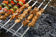 Beef and chicken kebab. Fresh meat at grill, bbq. Raw kebab grilling on metal skewer. Meat roasting at barbecue with vegetables. BBQ fresh beef chop slices Royalty Free Stock Photography
