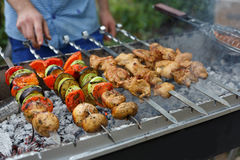Beef and chicken kebab. Fresh meat at grill, bbq. Raw kebab grilling on metal skewer. Meat roasting at barbecue with vegetables. BBQ fresh beef chop slices Royalty Free Stock Photo