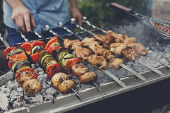 Beef and chicken kebab. Fresh meat at grill, bbq. Raw kebab grilling on metal skewer. Meat roasting at barbecue with vegetables. BBQ fresh beef chop slices Stock Image