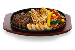 Beef chicken and shrimp fajitas. On a iron cast sizzling plate Stock Image