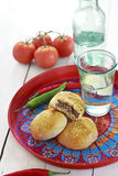 Beef and chili buns. With sesame seeds on a colourful old plate. Rustic country style royalty free stock photos