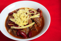 Beef chili and cheese in bowl over red Stock Photography