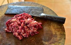 Beef. Chopped fresh beef preparation cooking on wooden butcher with cleaver Stock Image