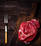 Beef on a chopping board and fork on dark wooden table. Style rustic. Beef on a chopping board and fork on dark wooden table. Style rustic, selective focus Stock Images
