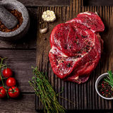 Beef on a chopping board, tomatoes,herbs, garlic and spices on dark wooden table . Royalty Free Stock Photography