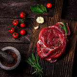Beef on a chopping board, tomatoes,herbs, garlic and spices on dark wooden table . Style rustic, selective focus Stock Images