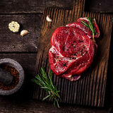 Beef on a chopping board, tomatoes,herbs, garlic and spices on dark wooden table . Stock Photos