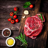 Beef on a chopping board, tomatoes,herbs and spices on dark wooden table. Royalty Free Stock Images