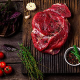 Beef on a chopping board, tomatoes,herbs and spices on dark wooden table. Style rustic. Stock Image