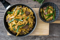 Beef chow mein in a frying pan. Chinese food. Beef chow mein in a frying pan on wood. Chinese food stock photography