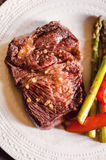 Beef chuck steak. Beef steak with green asparagus and roasted red bell pepper garnish Royalty Free Stock Images