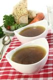 Beef Consomme. Two cups of Beef consomm� on a napkin Royalty Free Stock Image